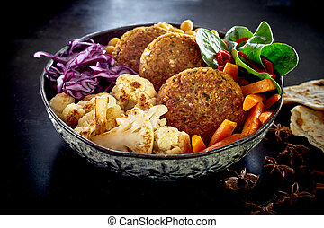 Close-up on bowl of vegetables and cutlets