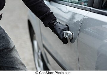 car thief hand pulling the handle of a car