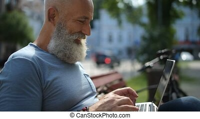 Close up on cheerful mature guy typing outdoors