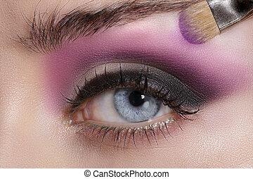 Close up on eyes , making colorful eyeshadows and eyeliner ...