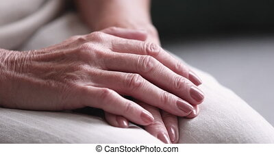 Close up on female wrinkled hands folded on knees. Depressed senior retired woman sitting with clasped arms, feeling loneliness indoors, retirement health problems, geriatric disease, poverty concept.