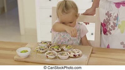 Close up on girl sprinkling toppings on muffins - Close up...
