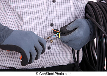 close-up on gloved hands of electrician at work