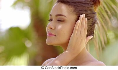 Close up on grinning woman near tropical tree - Close up on...