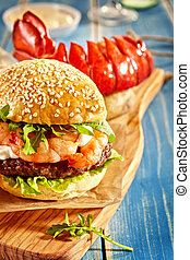 Close up on hamburger and lobster on table