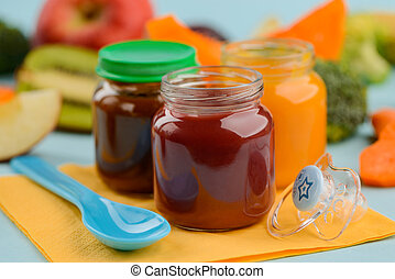 Close up on jars of fruit puree, spoon and pacifier
