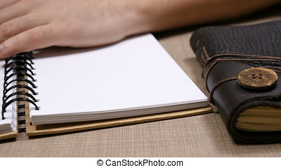Close up on man hand writing in a notebook