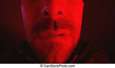 Close up on man with seductive facial expression biting his...