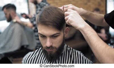 Close up on Men's hairstyling and haircutting in a barber...