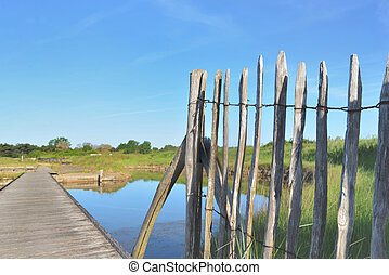 close up on natural wooden frence and walkway crossing  seawater ponds  under blue sky