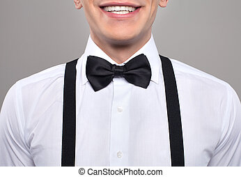 Close-up on nerd. Cropped image of young nerd man in bow tie and suspenders smiling while standing against grey background