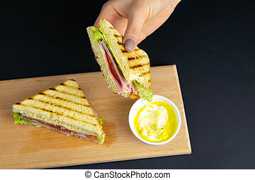 Close up on pair of young girl's hands removing a healthy wholesome wholemeal bread ham sandwich