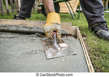Close up on paver smoothing fresh concrete