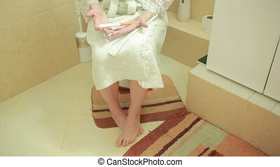 Close-up on pregnancy test. girl on the toilet