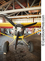 close up on propeller of yellow airplane in hangar, ready for take off