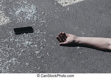 Close-up on smartphone and hand of a victim after traffic accident