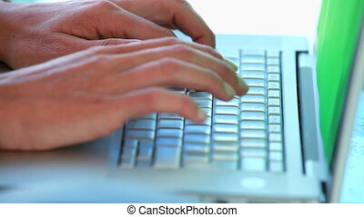 Close-up on someones's hands typing on a laptop in a bright...