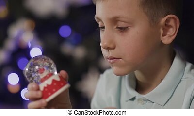 Close-up On the background of a blurred Christmas tree, the boy shakes a decorative toy ball in the middle of which is the Santa Clause