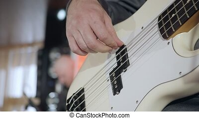 close up on the fingers of young man playing bass guitar on the stage
