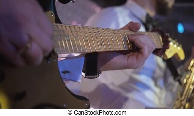 close up on the fingers of young man playing electric guitar on the stage
