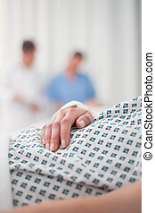 Close-up on the hand of a lying patient in a hospital
