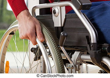 Close-up on wheelchair of capable disabled man