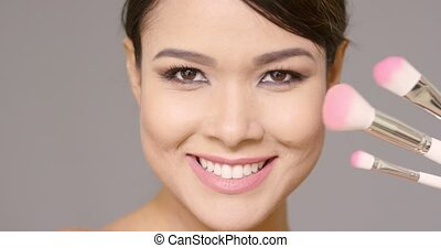 Close up on woman holding brushes in front of face