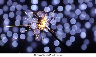 Close up one firework sparkler over blue bokeh