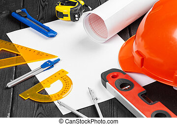 Close up orange hardhat and variety of repair tools with copy space in the middle over wooden background
