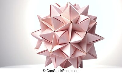 Close up origami spiky ball. Bright isolated background.