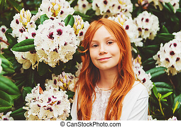 Close up outdoor portrait of adorable little girl of 8-9 year old . Red hair sweet young girl playing in spring garden