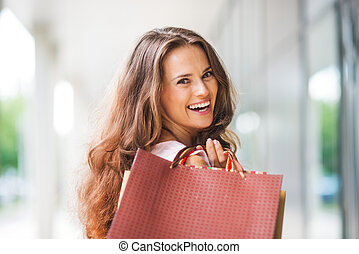 Close-up, over-the-shoulder smiling brown-haired woman...