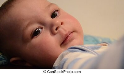 close up overhead shoot of baby boy lookig at the camera and...