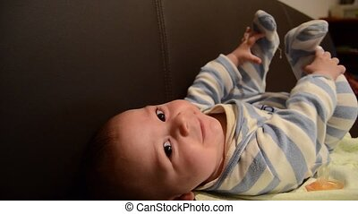 Close up overhead shot of baby boy on the soffa playing with...