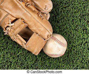 Close up overhead view of old leather baseball and mitt on grass turf field