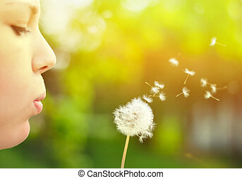 Close up ow woman blowing dandelion flower