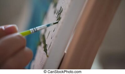 Close up paintbrush with acrylic paint. Woman painting a canvas with numbers. High quality FullHD footage