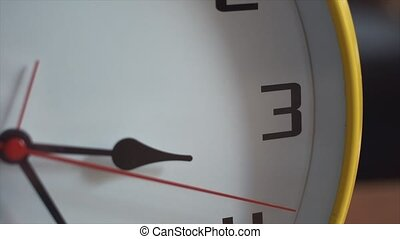 Close up pan shot of clock face with ticking second hand.