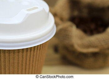 Close up paper cup of coffee with beans on sackcloth
