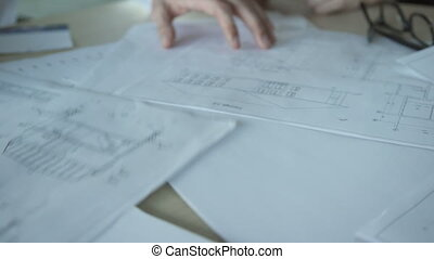 Close up papers with design drawings on meeting inside office.