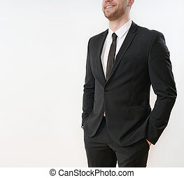 part of smiling business man in black suit with hands in pockets on white background