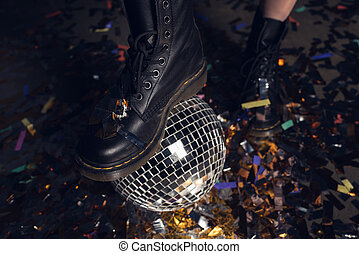 Close-up partial view of young woman in stylish shoes standing on shiny disco ball