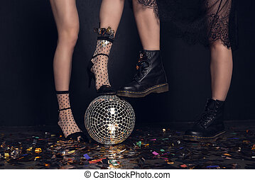 Close-up partial view of young women in stylish shoes standing on shiny disco ball