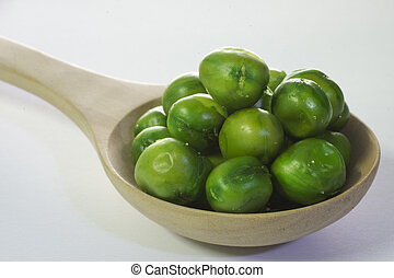 Close-up peas in wooden spoon on a white background