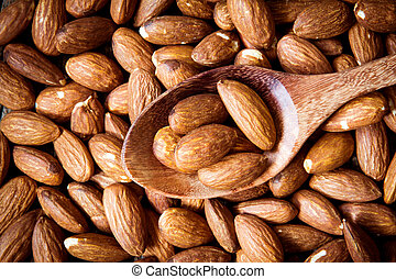 close up Peeled almonds nut in spoon on almond background