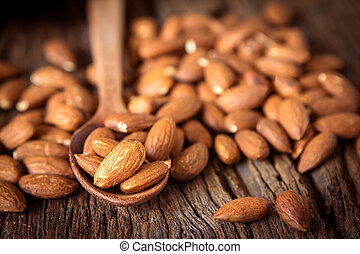 close up Peeled almonds nut in spoon on wooden background