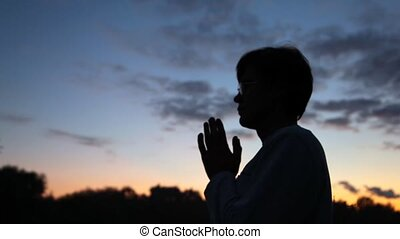 close up person prayerfully putting hands against wood at dawn
