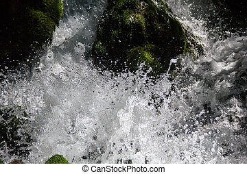 Close up photo of a fresh clean waterfall surrounded by green moss covered rocks