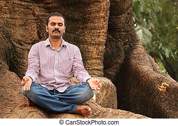 Close-up photo of a handsome indian executive doing meditation under a tree in a park. The person is sitting in lotus posture and is calm, relaxed closing his eyes for better concentration