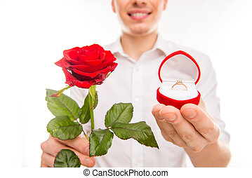 Close up photo of a handsome man with a red rose and wedding ring